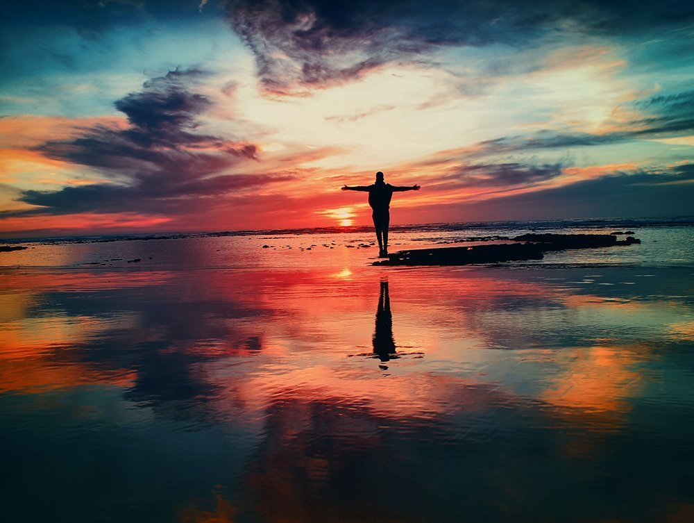 coastal sunset with person reaching arms out to the sky
