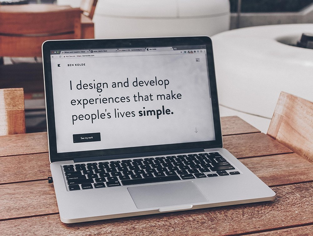 Laptop showing text I design and develop experiences that make people's lives simple